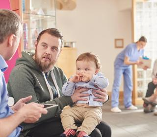 GP holding a tablet computer interviews a father with a baby in the waiting room, in the background a practice nurse shows notes to two patients