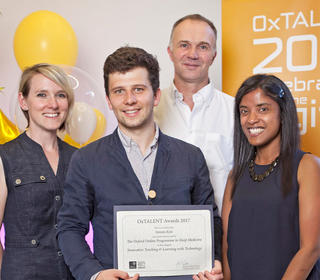 Staff from MSD pose with a certificate in front of an OxTALENT 2017 banner and balloons