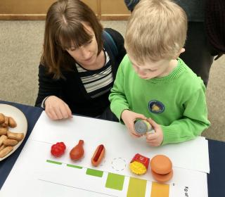 A child and his mother use plastic food in in our GHG game